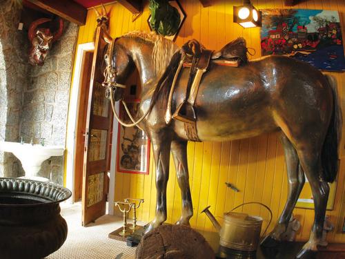 """O cavalo de Temuco, restaurado por presentes de amigos do poeta. Neruda dizia que era o único cavalo do mundo com rabo de três cores. A porta à esquerda, acima, é de um pequeno banheiro """"só para homens"""" e decorado com postais eróticos antigos."""