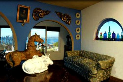 Sala de estar do terceiro andar de La Sebastiana. A vaca de porcelana no centro da mesa era usada por Neruda para servir ponches a seus convidados.
